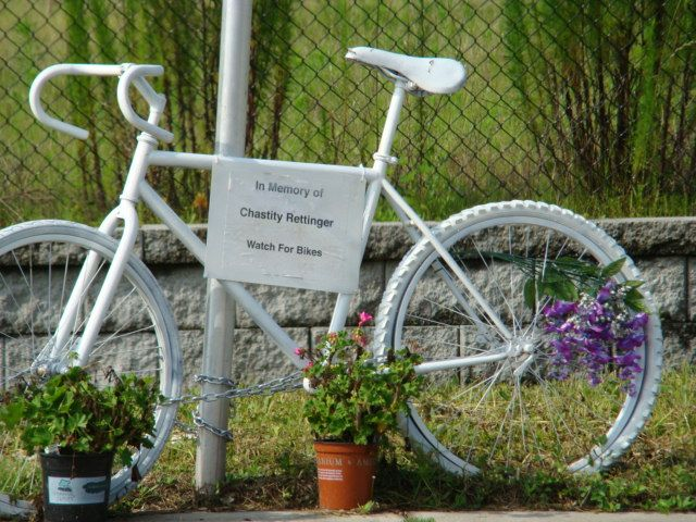 white-painted ghost bike with sign reading 'in memory of Chastity Rettinger; watch for bikes' and live flowers decorating