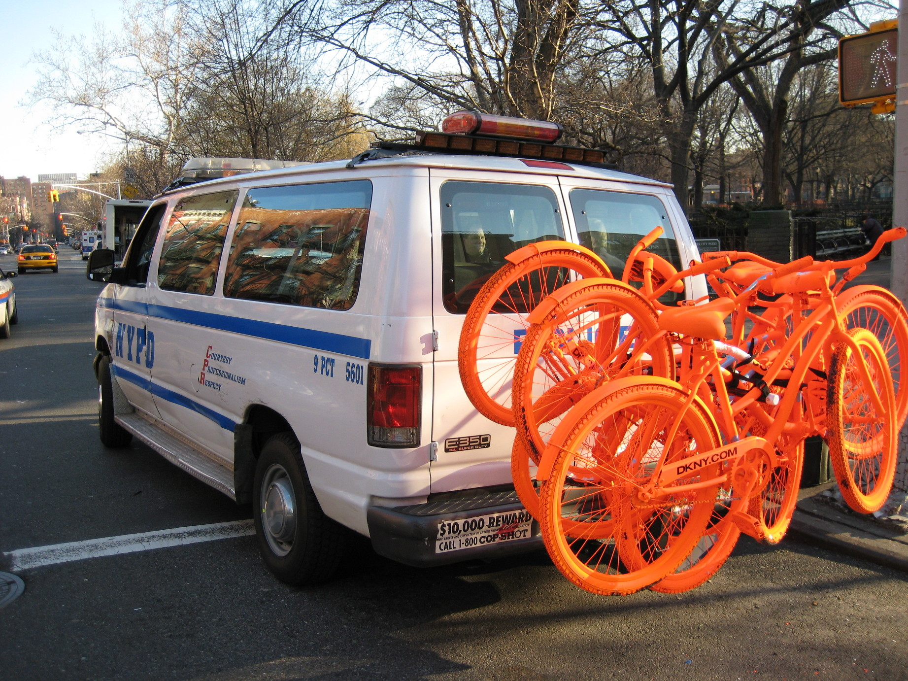 NYPD Van with five orange DKNY bikes on the back