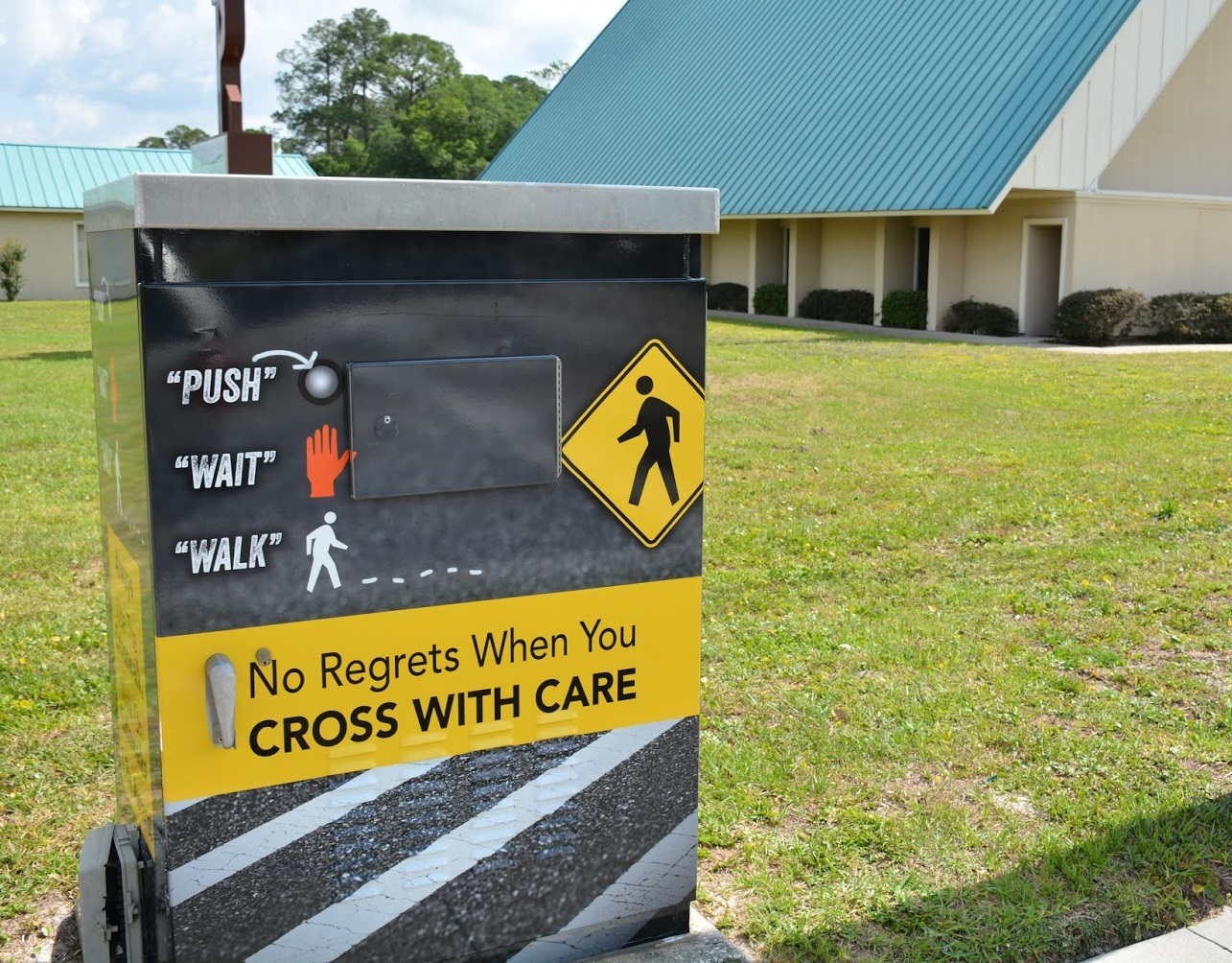 Public service poster instructs pedestrians in safe crossings and reads, 'no regrets when you cross with care'