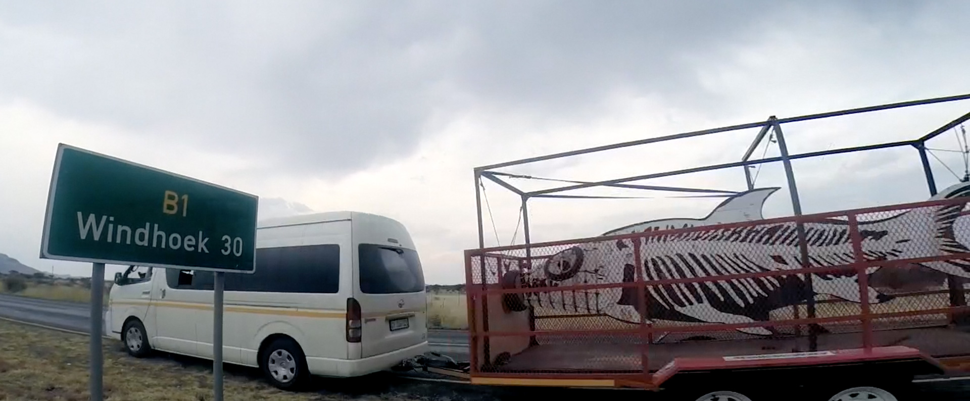 Images depict the fish on the final leg of the trip to Windhoek. A van tows the fish in the cage past a sign for Windhoek.